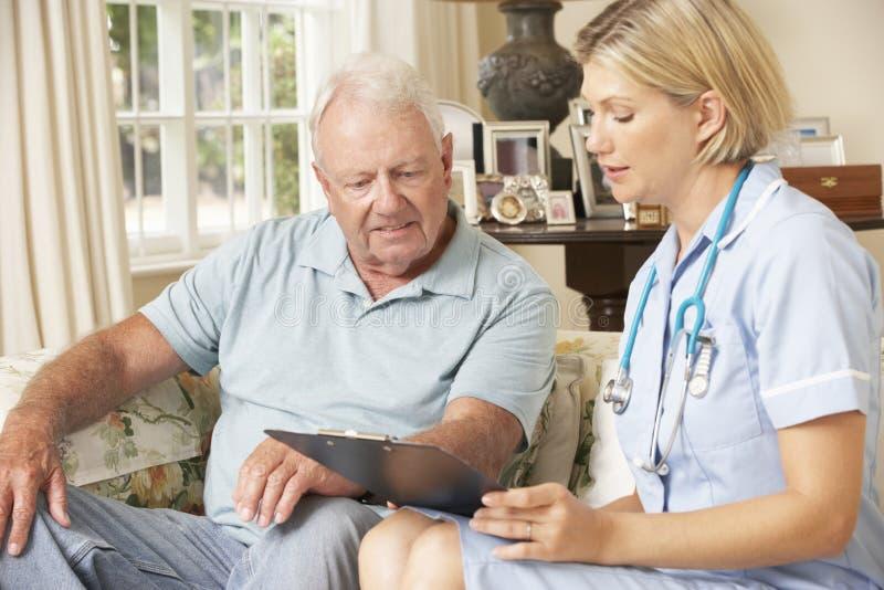 Συνταξιούχο ανώτερο άτομο που έχει τον έλεγχο υγείας με τη νοσοκόμα στο σπίτι στοκ εικόνες