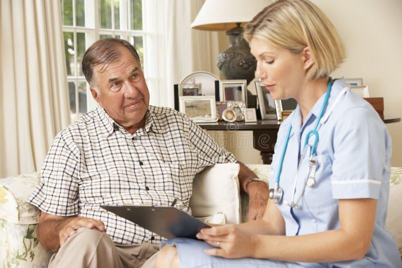 Συνταξιούχο ανώτερο άτομο που έχει τον έλεγχο υγείας με τη νοσοκόμα στο σπίτι στοκ εικόνα