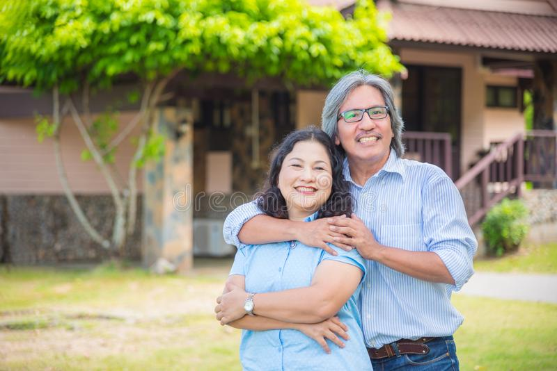 Συνταξιούχο ζεύγος που στέκεται μπροστά από το σπίτι και το χαμόγελό τους στοκ εικόνες με δικαίωμα ελεύθερης χρήσης