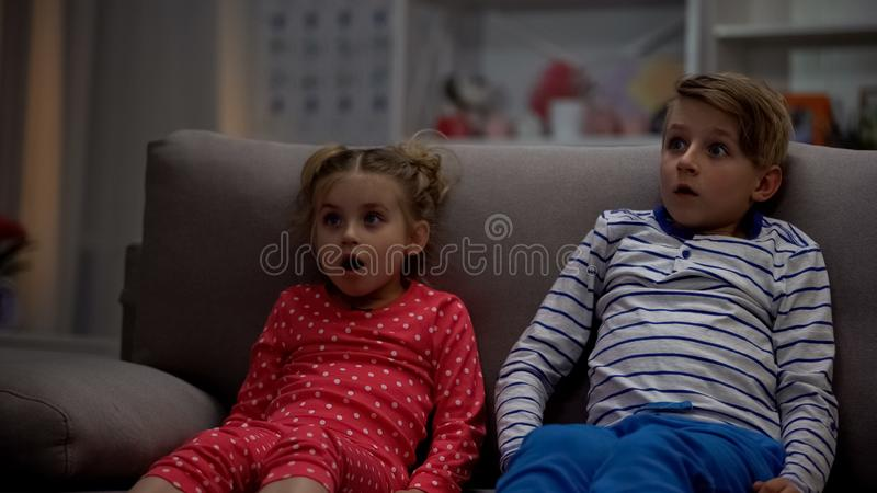 Συντριμμένη ταινία φρίκης προσοχής αδελφών και αδελφών τη νύχτα, που κάθεται τον καναπέ στοκ εικόνα με δικαίωμα ελεύθερης χρήσης