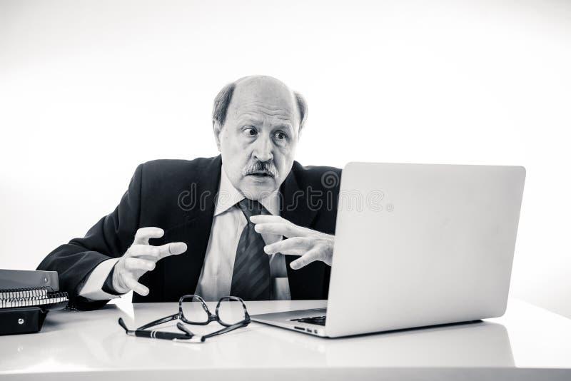 Συντριμμένος και κουρασμένος παλαιός επιχειρηματίας που εργάζεται με το lap-top που αισθάνεται στο γραφείο στοκ φωτογραφίες με δικαίωμα ελεύθερης χρήσης