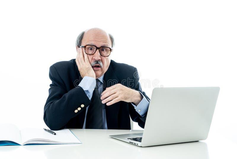 Συντριμμένος και κουρασμένος παλαιός επιχειρηματίας που εργάζεται με το lap-top που αισθάνεται στο γραφείο στοκ φωτογραφία με δικαίωμα ελεύθερης χρήσης