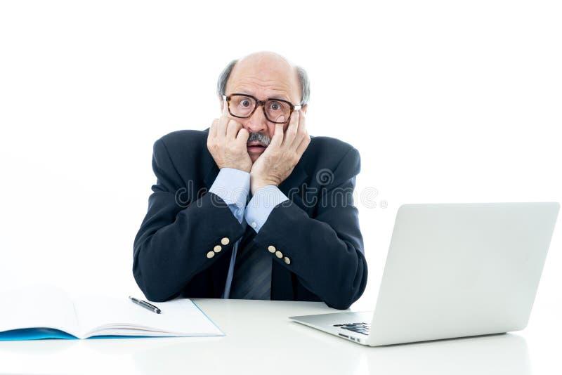 Συντριμμένος και κουρασμένος παλαιός επιχειρηματίας που εργάζεται με το lap-top που αισθάνεται στο γραφείο στοκ φωτογραφίες