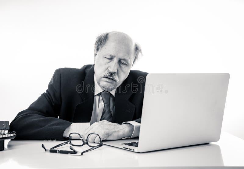 Συντριμμένος και κουρασμένος παλαιός επιχειρηματίας που εργάζεται με το lap-top που αισθάνεται στο γραφείο στοκ εικόνες