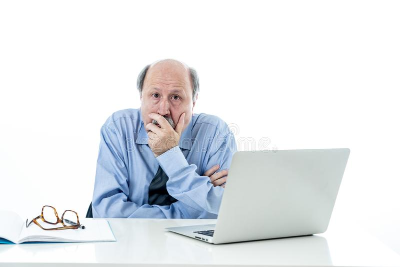 Συντριμμένος και κουρασμένος παλαιός επιχειρηματίας που εργάζεται με το lap-top που αισθάνεται στο γραφείο στοκ εικόνα