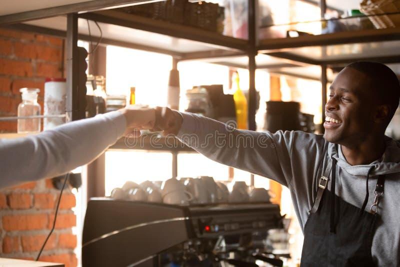 Συντροφικοί εργαζόμενοι καφέδων που χαιρετούν ο ένας τον άλλον στην πρόσκρουση πυγμών εργασίας στοκ εικόνες με δικαίωμα ελεύθερης χρήσης