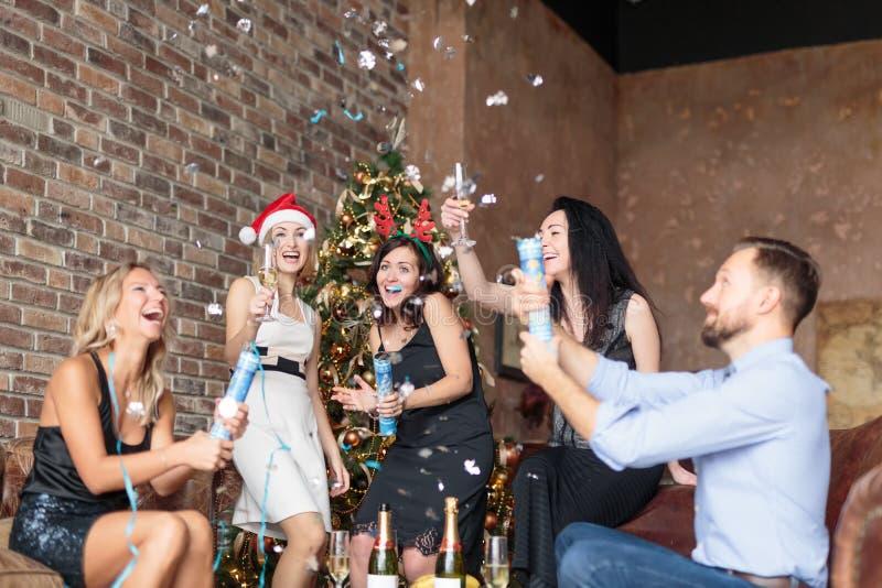 Συντροφικοί συνάδελφοι που έχουν τη διασκέδαση με το confettin στο νέο κόμμα έτους ` s στο σύγχρονο γραφείο ύφους σοφιτών στοκ εικόνες