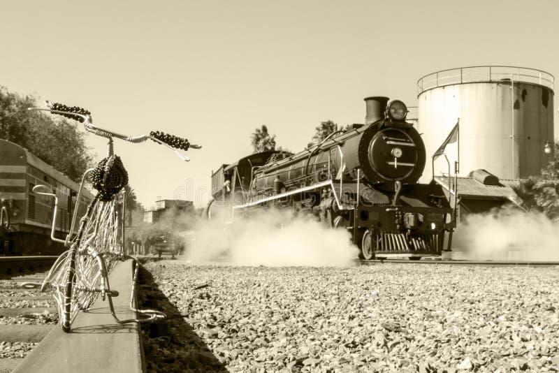 Συνδεμένο με καλώδιο ποδήλατο με το τραίνο ατμού στοκ φωτογραφίες