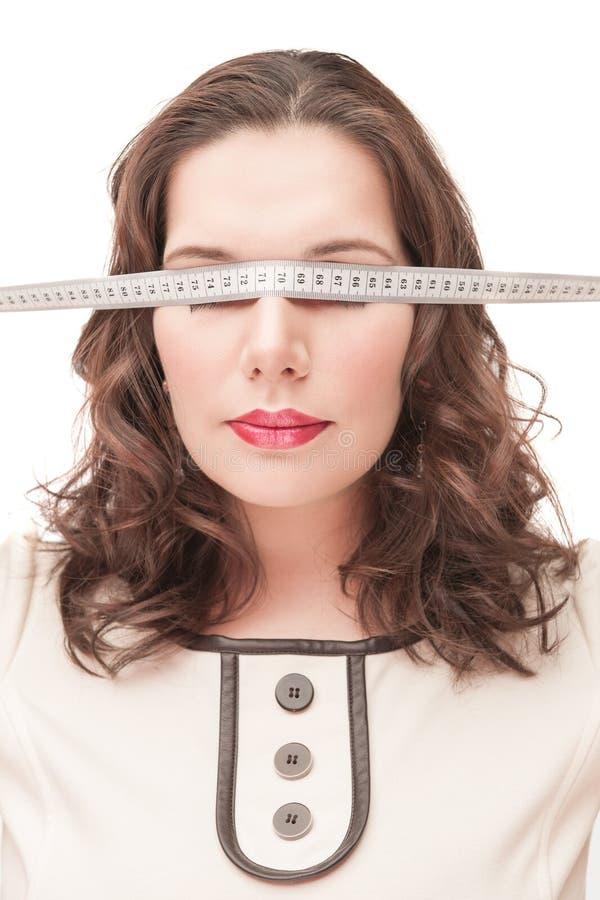 Συν τη γυναίκα μεγέθους blindfold με το εκατοστόμετρο στοκ εικόνα με δικαίωμα ελεύθερης χρήσης