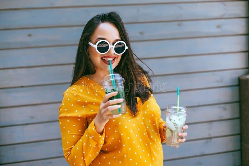 Συν το μέγεθος η κατανάλωση γυναικών παίρνει μαζί το κοκτέιλ πέρα από τον τοίχο καφέδων πόλεων στοκ εικόνα