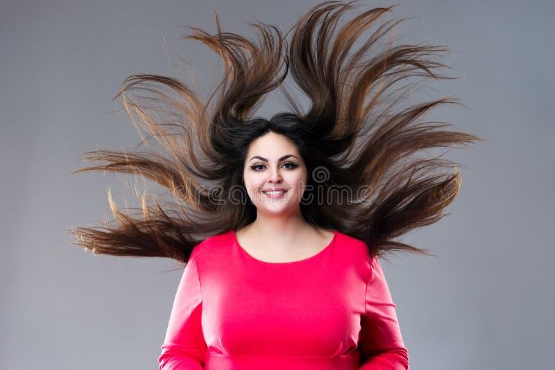 Συν το πρότυπο μεγέθους με το μακρυμάλλες φύσηγμα στον αέρα, παχιά γυναίκα brunette στο γκρίζο υπόβαθρο, θετική έννοια σωμάτων στοκ εικόνα
