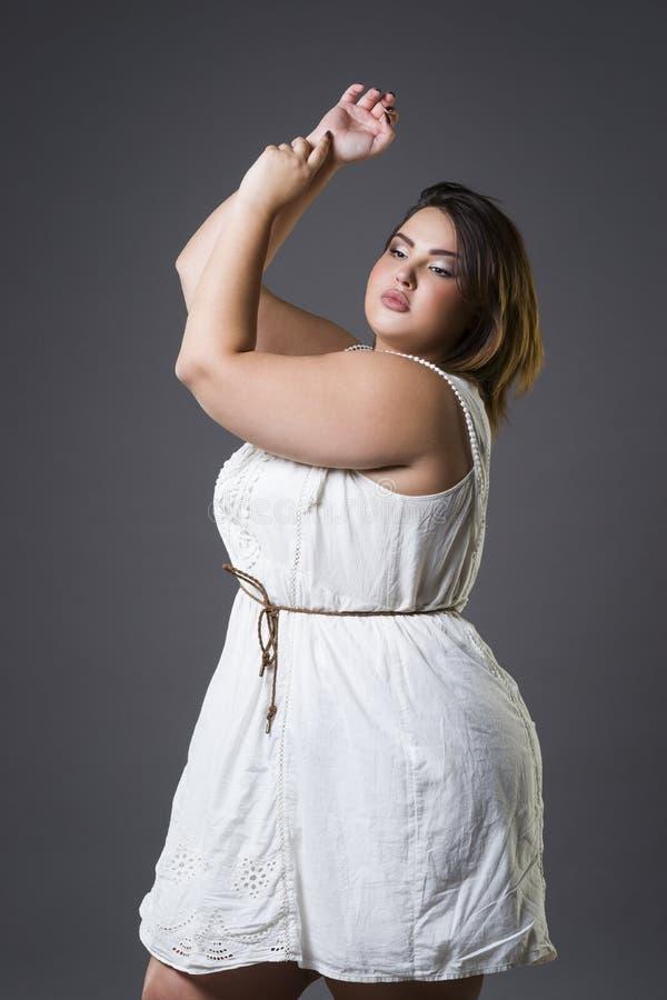 Συν το πρότυπο μόδας μεγέθους στα περιστασιακά ενδύματα, παχιά γυναίκα στο γκρίζο υπόβαθρο, υπέρβαρο θηλυκό σώμα στοκ φωτογραφία με δικαίωμα ελεύθερης χρήσης