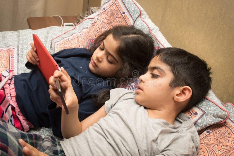 Συσκευές μεριδίου αδελφών και αδελφών στην ώρα για ύπνο στοκ εικόνες