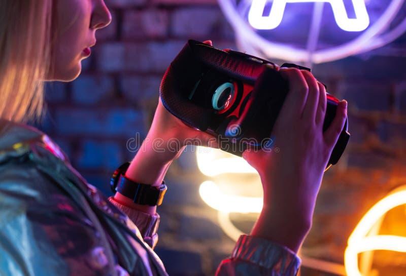 Συσκευή γυαλιών κασκών εκμετάλλευσης γυναικών vr που φωτίζεται με το φουτουριστικό φως νέου στοκ εικόνες