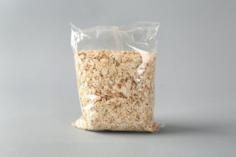 Συσκευασία με ακατέργαστο oatmeal στο ελαφρύ υπόβαθρο στοκ φωτογραφίες