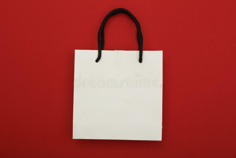 Συσκευασία τσαντών της Λευκής Βίβλου στο κόκκινο υπόβαθρο r Χλεύη επάνω στην έννοια για το τύλιγμα δώρων στοκ φωτογραφίες
