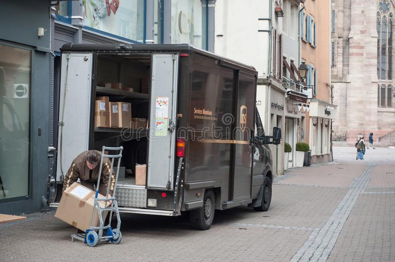 Συσκευασίες εκφόρτωσης εργαζομένων παράδοσης UPS από το φορτηγό του στην οδό στοκ εικόνες