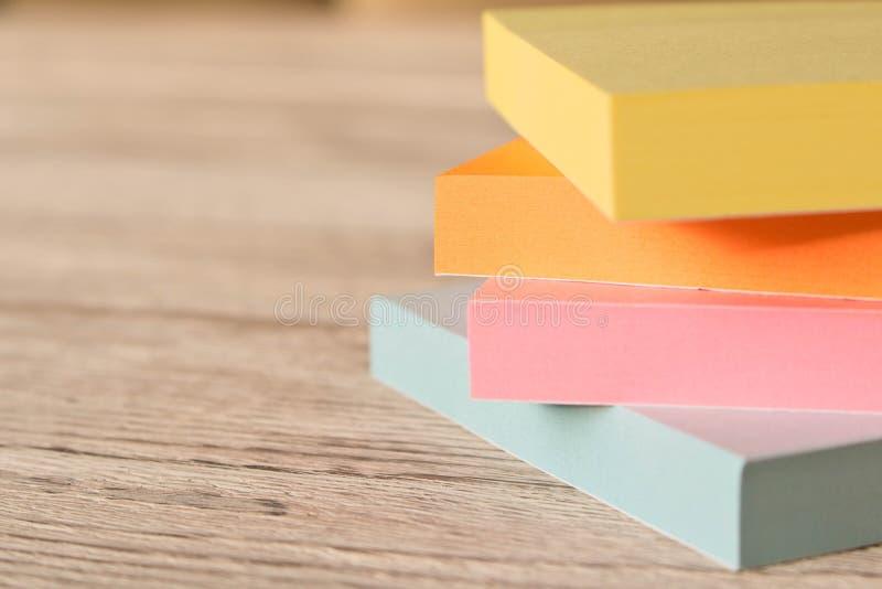 Συσκευασίες των ζωηρόχρωμων αυτοκόλλητων ετικεττών για τις σημειώσεις για έναν ξύλινο πίνακα στοκ φωτογραφία