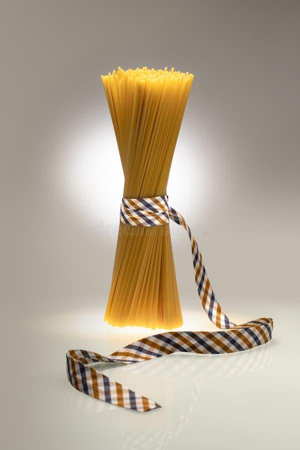 Συσκευασμένα μακαρόνια μόδας που δένονται με την κορδέλλα στο δις-χρωματισμένο υπόβαθρο στοκ εικόνες