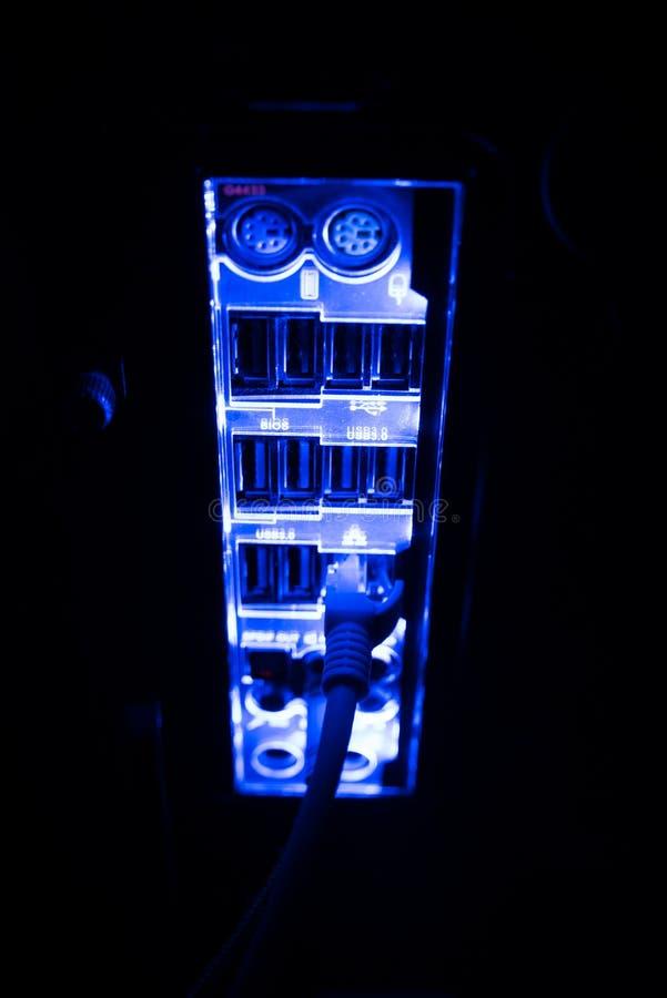 Συσκότιση, θολωμένα σύνορα Κλείστε επάνω των μπλε καλωδίων δικτύων που συνδέονται με το μαύρο διακόπτη που καίγεται στο σκοτάδι στοκ φωτογραφία