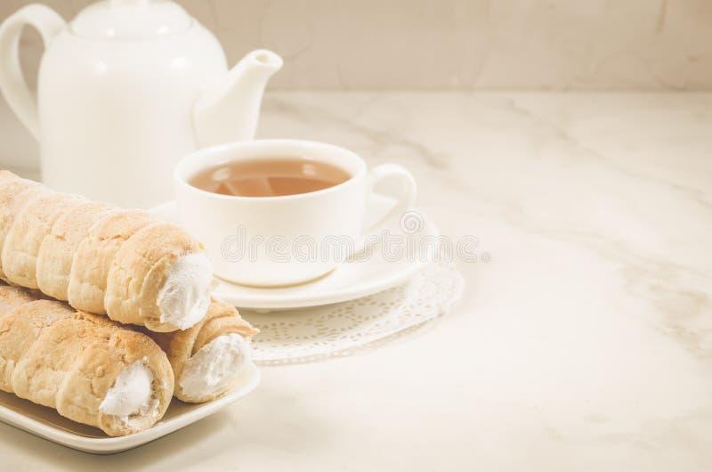 Συσσωματώστε tubule με την άσπρη κατανάλωση τσαγιού φλυτζανιών κρέμας και τσαγιού με τα κέικ κρέμας σε ένα άσπρο μαρμάρινο υπόβαθ στοκ εικόνα