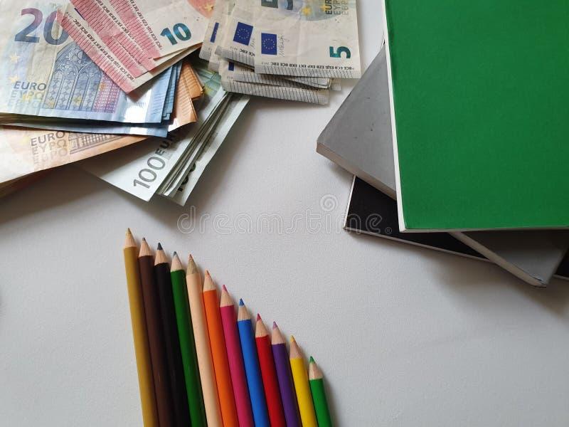 συσσωρευμένα βιβλία, μολύβια χρώματος και ευρωπαϊκά τραπεζογραμμάτια των διαφορετικών μετονομασιών στον πίνακα στοκ εικόνα με δικαίωμα ελεύθερης χρήσης