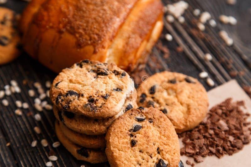 Συσσωρευμένα μπισκότα τσιπ σοκολάτας και κουλούρι κανέλας με τη σοκολάτα στην καφετιά πετσέτα στοκ εικόνες