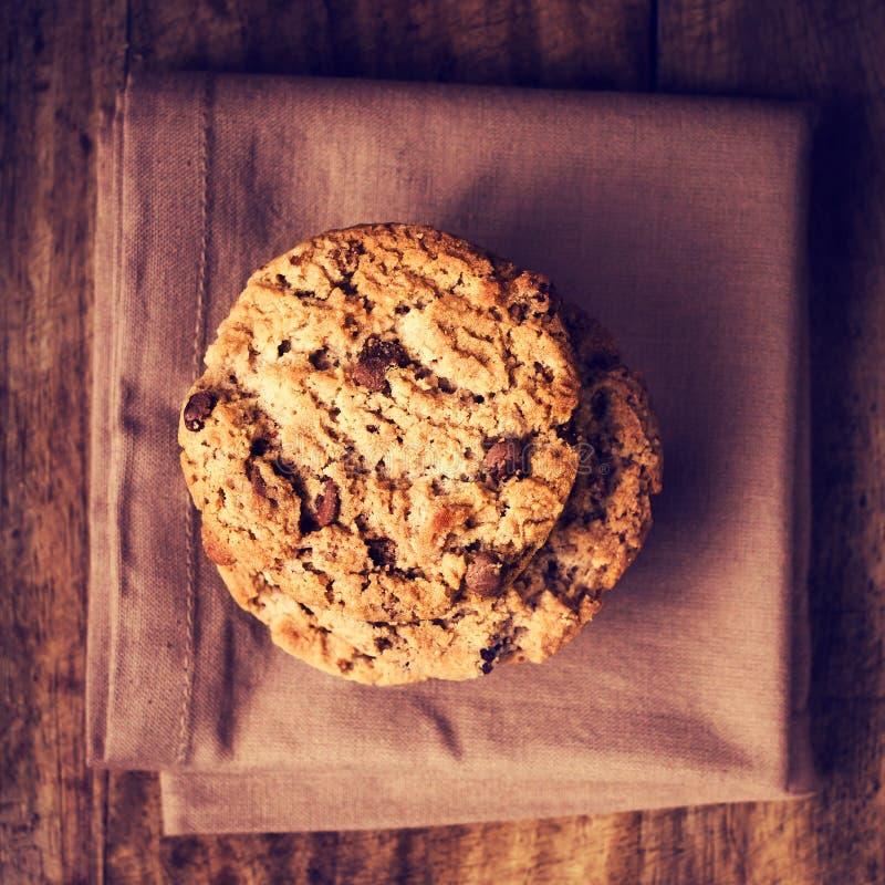 Συσσωρευμένα μπισκότα τσιπ σοκολάτας στην καφετιά πετσέτα πέρα από το ξύλινο backg στοκ φωτογραφία με δικαίωμα ελεύθερης χρήσης