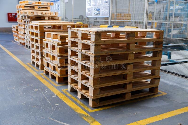 Συσσωρευμένες ξύλινες παλέτες σε μια αποθήκευση στοκ εικόνα