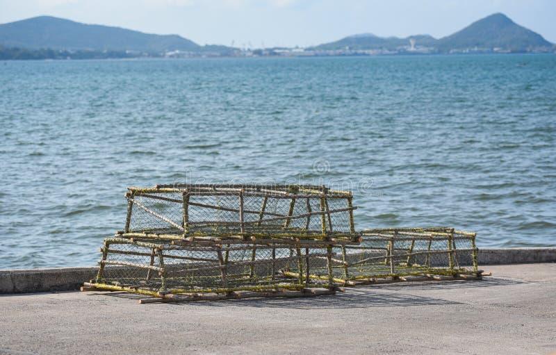 Συσσωρευμένο δοχεία δίχτυ του ψαρέματος αστακών και καβουριών που πιάνει στον κόλπο στοκ εικόνες
