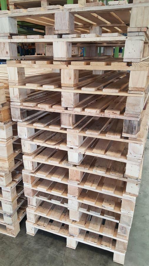 Συσσώρευση του νέου όρου των καφετιών ξύλινων παλετών για τη διανομή και τη μεταφορά προϊόντων στην αποθήκη εμπορευμάτων στοκ φωτογραφία με δικαίωμα ελεύθερης χρήσης