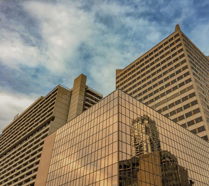 Συστάδα κτηρίων πολυόροφων κτιρίων με την αντανακλαστική χρυσή πυράκτωση στοκ φωτογραφία