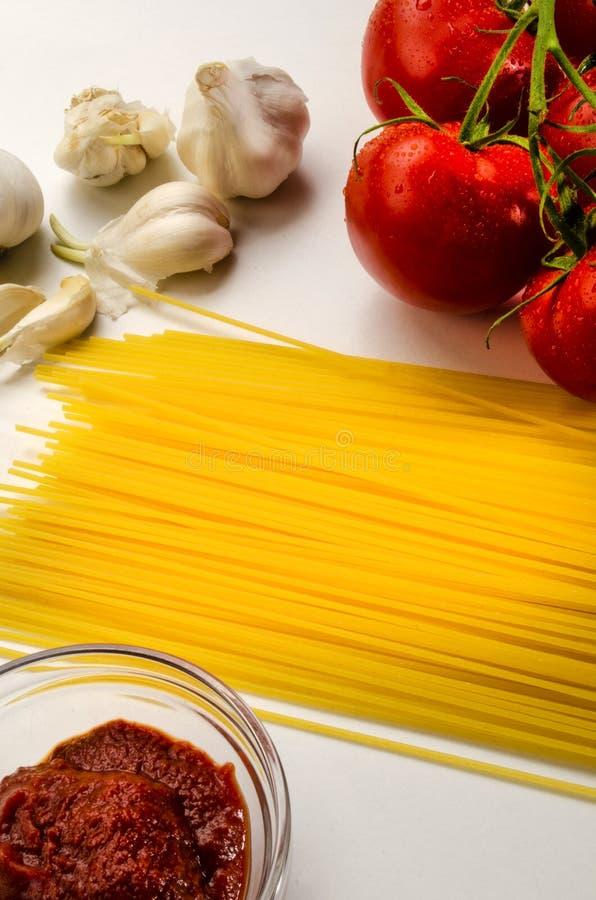 Συστατικά για να κάνει μια εύγευστη οργανική σάλτσα ντοματών με τα μακαρόνια στοκ εικόνες