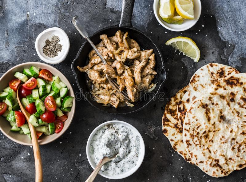 Συστατικά για τα ελληνικά γυροσκόπια κοτόπουλου - τηγανισμένο κοτόπουλο, σαλάτα αγγουριών ντοματών, σάλτσα tzatziki και flatbread στοκ φωτογραφία με δικαίωμα ελεύθερης χρήσης