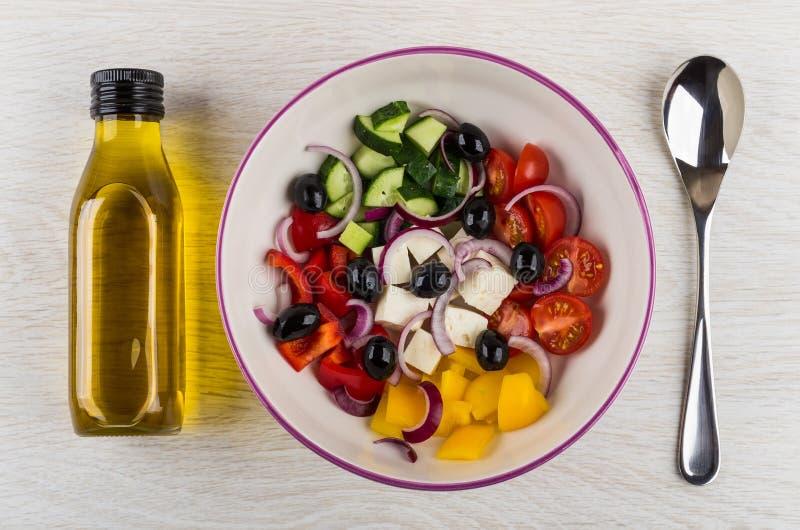 Συστατικά για την ελληνική σαλάτα στο κύπελλο, μπουκάλι του πετρελαίου, κουτάλι στοκ εικόνες με δικαίωμα ελεύθερης χρήσης