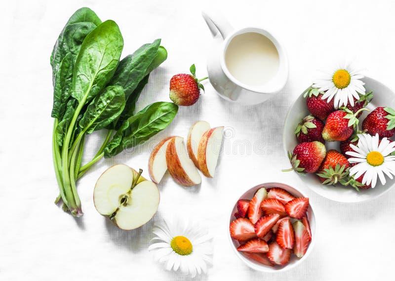 Συστατικά για την κατασκευή της καρύδας το probiotic γιαούρτι, σπανάκι, μήλο, καταφερτζής φραουλών detox σε ένα ελαφρύ υπόβαθρο,  στοκ φωτογραφία με δικαίωμα ελεύθερης χρήσης