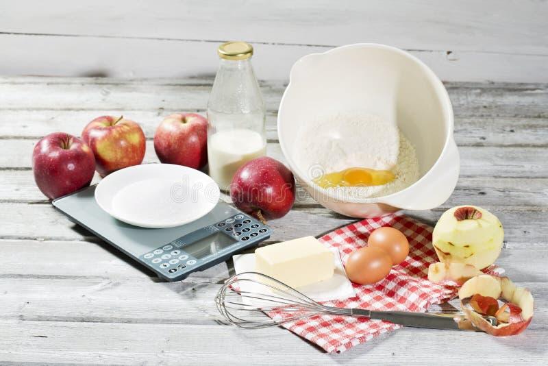 Συστατικά για την πίτα, τα μήλα, το βούτυρο, τα αυγά, το αλεύρι, το γάλα και τη ζάχαρη μήλων στοκ εικόνα με δικαίωμα ελεύθερης χρήσης