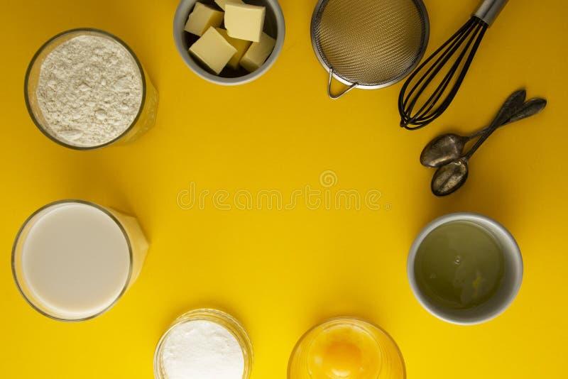 Συστατικά για τη ζύμη ή το επιδόρπιο ψησίματος - βούτυρο, αλεύρι, αυγά, γάλα, ζάχαρη Το κίτρινο υπόβαθρο, επίπεδο βάζει Συνταγή ε στοκ εικόνες με δικαίωμα ελεύθερης χρήσης
