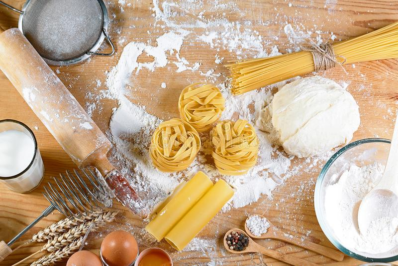 Συστατικά για τη ζύμη, μαγειρεύοντας μακαρόνια ζυμαρικών tagliatelle, συμπεριλαμβανομένου του αλευριού, αυγά, γάλα, στο ξύλινο αγ στοκ εικόνες με δικαίωμα ελεύθερης χρήσης