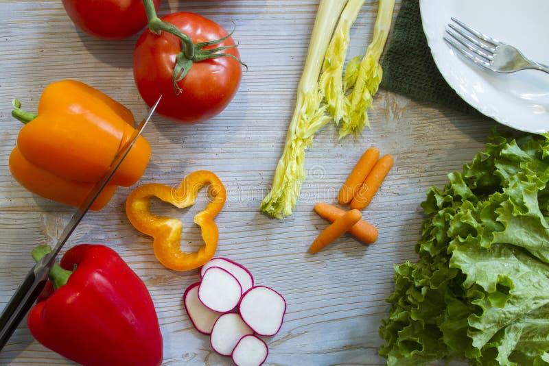 Συστατικά για τη φρέσκια σαλάτα στους ξύλινους πίνακες με το κύπελλο και τον αρχιμάγειρα στοκ εικόνα με δικαίωμα ελεύθερης χρήσης