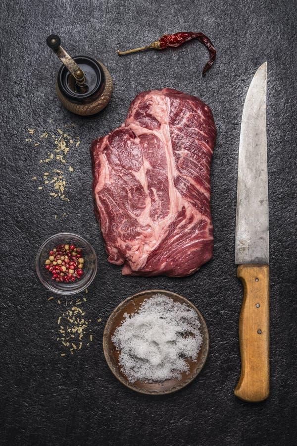 Συστατικά για το μαγείρεμα της μπριζόλας βόειου κρέατος με το χαράζοντας μαχαίρι αλατιού και πιπεριών, μύλος πιπεριών σε μια σκοτ στοκ εικόνες