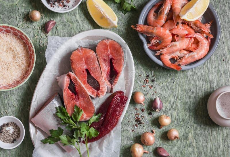 Συστατικά για το μαγείρεμα του μεσημεριανού γεύματος - φρέσκα κόκκινα ψάρια, γαρίδες, ρύζι, καρυκεύματα Σε έναν ξύλινο πίνακα, το στοκ εικόνες με δικαίωμα ελεύθερης χρήσης