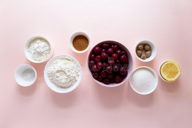 Συστατικά για το μαγείρεμα του σπιτικού κέικ δικτυωτού πλέγματος κερασιών στο ρόδινο υπόβαθρο Παραδοσιακά αμερικανικά τρόφιμα r στοκ εικόνες