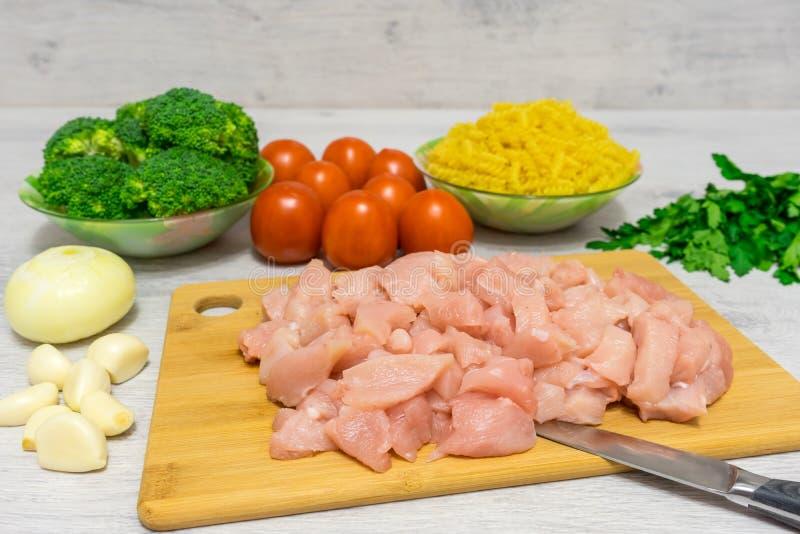 Συστατικά για το μαγείρεμα των ζυμαρικών με το κοτόπουλο και το μπρόκολο στοκ εικόνες