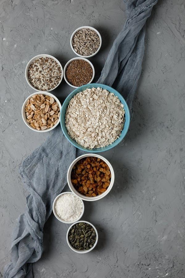 Συστατικά για το σπιτικό granola μαγειρέματος: oatmeal, σταφίδες, τσιπ καρύδων, μέλι, φυστίκια, κακάο, βακκίνια, φυτικά στοκ εικόνα με δικαίωμα ελεύθερης χρήσης