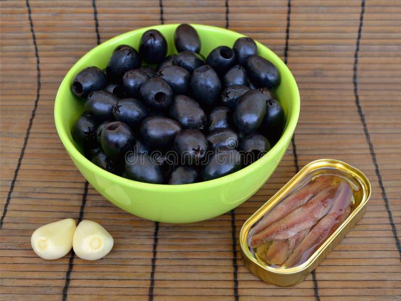 Συστατικά για το tapenade: λιθοστρωμένες μαύρες ελιές σε ένα πράσινο κύπελλο, λωρίδες αντσουγιών σε ένα κίτρινο ωοειδές δοχείο κα στοκ εικόνα
