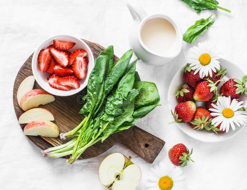 Συστατικά καταφερτζήδων - σπανάκι, φράουλα, μήλο, γιαούρτι καρύδων σε ένα άσπρο υπόβαθρο, τοπ άποψη στοκ εικόνες