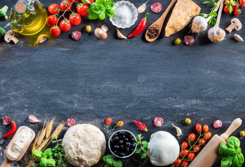 Συστατικά πιτσών στο μαύρο πίνακα σε έναν ακατέργαστο στοκ εικόνα