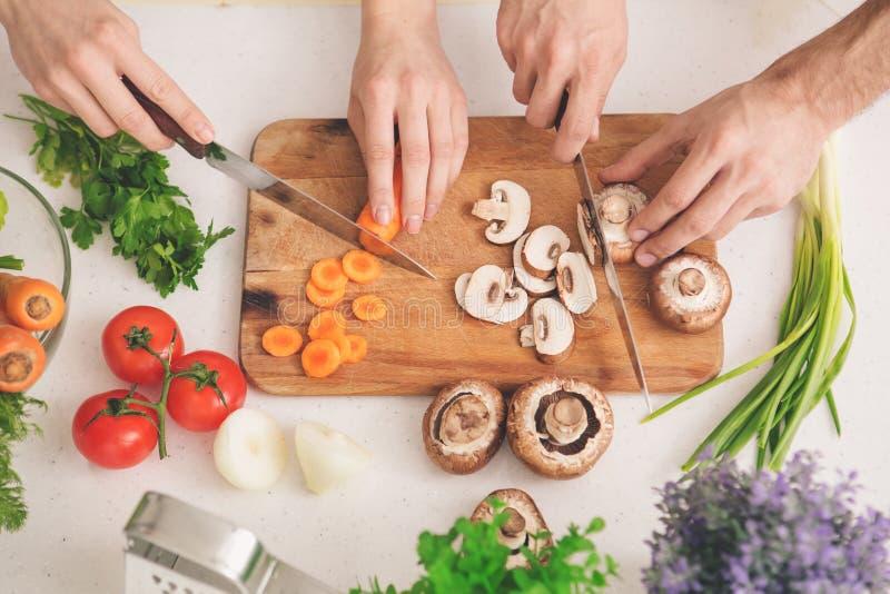 Συστατικά προετοιμασιών οικογενειακού μαγειρεύοντας γεύματος τέμνοντα μαζί στοκ φωτογραφία