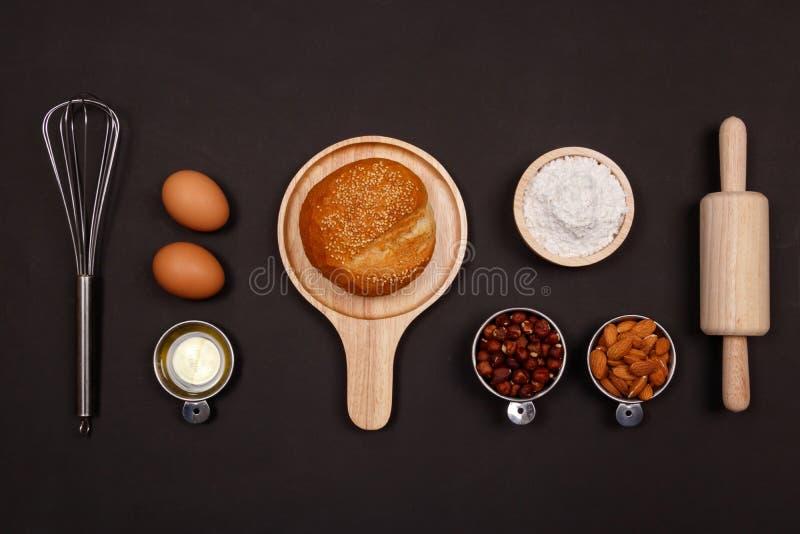 Συστατικά ψωμιού στο μαύρο υπόβαθρο Έννοια προγευμάτων μαγειρέματος στοκ φωτογραφίες